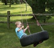 使用在轮胎摇摆的孩子 免版税库存图片