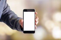 使用在迷离背景的人智能手机 免版税库存照片