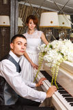 使用在钢琴的婚礼夫妇 库存照片