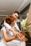 使用在钢琴的婚礼夫妇 库存图片
