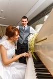 使用在钢琴的婚礼夫妇 免版税图库摄影