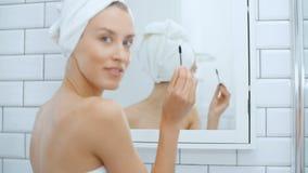 使用在镜子前面的年轻快乐的妇女染睫毛油 股票录像