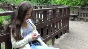 使用在长凳的年轻可爱的女孩手机 在公园空白夏天的结构树的云彩 微笑 HD射击运动照相机全景与 股票录像