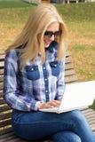 使用在长凳的美丽的妇女膝上型计算机在公园 免版税库存照片