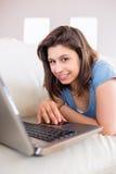 使用在长沙发的俏丽的浅黑肤色的男人膝上型计算机 图库摄影