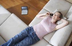 使用在长沙发的妇女手机 库存图片