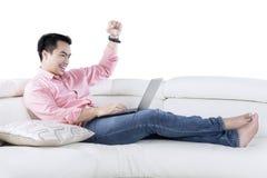 使用在长沙发的愉快的人膝上型计算机 免版税库存图片