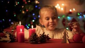 使用在闪耀的X-mas树,木装饰附近的愉快的微笑的女孩为假日 库存图片