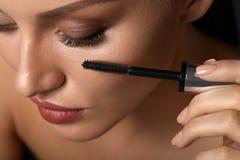 使用在闭合的眼睛的美丽的妇女黑染睫毛油 库存照片