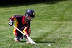 使用在防护齿轮曲棍网兜球的小男孩在公园 免版税库存图片