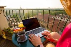 使用在阳台的妇女便携式计算机 免版税库存照片