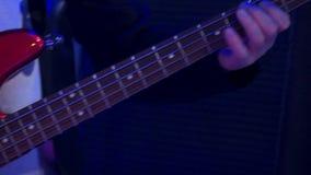 使用在阶段的电低音吉他的特写镜头男性音乐家手在表现期间在党 股票录像