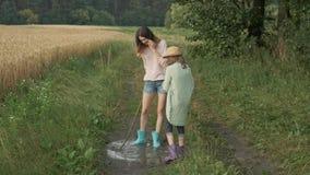 使用在雨水水坑的起动的两个愉快的女孩姐妹在乡下公路的 影视素材