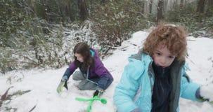 使用在雪和投掷的雪球的孩子 股票录像