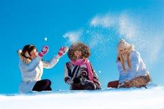 使用在雪球的快乐的女孩户外 图库摄影