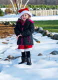 使用在雪的圣诞老人帽子的小女孩 图库摄影