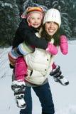 使用在雪的母亲和女儿 免版税库存图片