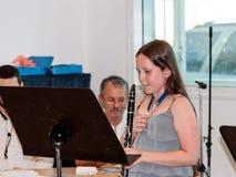 使用在音乐课的一个教训的女孩实践的长笛  免版税库存照片