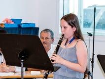 使用在音乐课的一个教训的女孩实践的长笛  库存照片