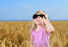 使用在麦田的逗人喜爱的矮小的白肤金发的女孩 免版税库存图片