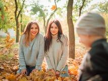 使用在黄色叶子和姐妹的一个小男孩的特写镜头 库存图片