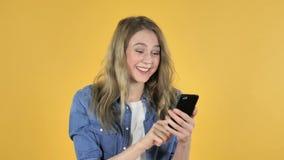 使用在黄色背景时的智能手机为成功激发的年轻俏丽的女孩,当 影视素材