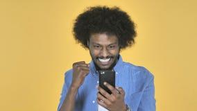 使用在黄色背景时的智能手机为成功激发的美国黑人的人,当 影视素材