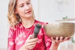 使用在黄铜西藏唱歌碗的年轻女人 合理的疗法和凝思 库存照片