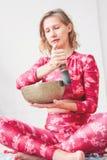 使用在黄铜西藏唱歌碗的年轻女人 合理的疗法和凝思 图库摄影
