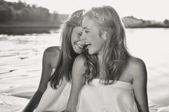 使用在水中的两个愉快的女孩黑白色摄影在日落海滩 太阳火光背景 库存照片