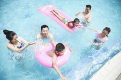 使用在水中的家庭和朋友在与可膨胀的管的水池 免版税库存图片