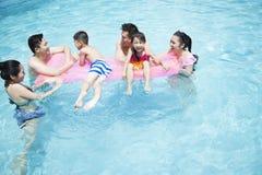 使用在水中的家庭和朋友在水池 免版税库存图片