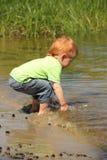 使用在水中的红色头发男孩 库存图片