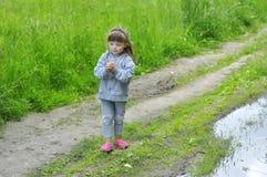 使用在水坑的橡胶鞋子的小女孩在夏天森林里 库存图片