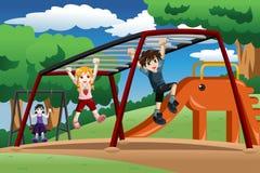 使用在猴子栏杆的孩子在操场 免版税图库摄影