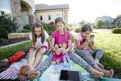 使用在他们巧妙的电话的三个小女孩而不是谈话 免版税库存照片