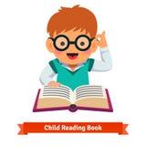 使用在玻璃阅读书的小男孩 免版税库存图片
