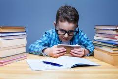 使用在他的电话的年轻学生在教室 免版税图库摄影