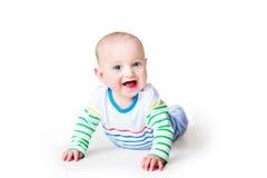 使用在他的肚子的愉快的笑的男婴 免版税库存照片