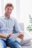 使用在他的长沙发的英俊的人一台片剂个人计算机 免版税库存图片