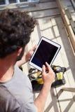 使用在建筑工地的建筑工人数字式片剂 免版税库存照片