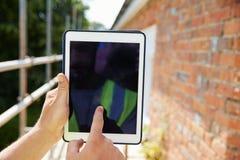 使用在建筑工地的建筑工人数字式片剂 免版税库存图片