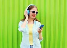 使用在绿色的智能手机相当凉快的妇女听到在耳机的音乐 免版税库存照片