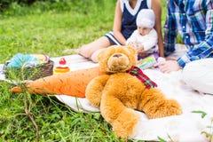使用在绿草的婴孩和母亲和父亲,家庭野餐特写镜头 库存图片