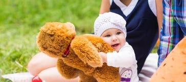 使用在绿草的婴孩和母亲和父亲,家庭野餐特写镜头 免版税库存图片