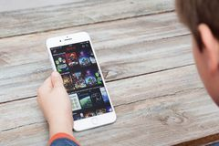 使用在iPhone 7的男孩Netflix正 免版税库存图片