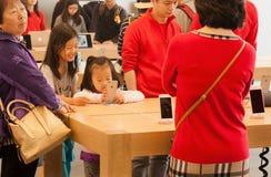 使用在iStore里面的未认出的女孩智能手机与许多iPhones和小配件 免版税库存图片