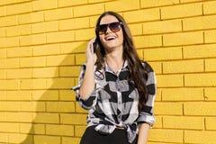 使用在yello前面的一名别致的妇女的画象手机 免版税库存图片