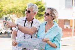 使用地图的愉快的旅游夫妇在城市 图库摄影
