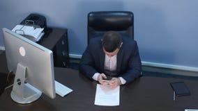 使用坐在书桌的智能手机的有胡子的商人在办公室 库存照片